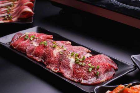 Raw beef slice for barbecue japanese style, yakiniku, meat are being cooked on stove in Japanese restaurant. Standard-Bild - 157190280