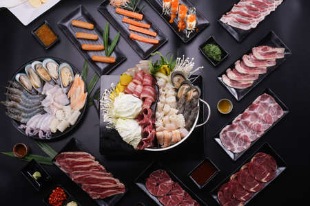 Shabu Shabu or Sukiyaki, a popular dish of pork, beef, shrimp, squid, seafood and fresh vegetables. Placed on a table with a boiling pot boiling in a Japanese restaurant. Standard-Bild - 157107991