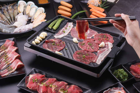 Raw beef slice for barbecue japanese style, yakiniku. Meats are being cooked on stove in a japanese restaurant.