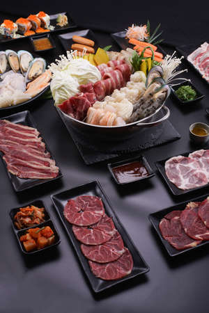Shabu Shabu or Sukiyaki, a popular dish of pork, beef, shrimp, squid, seafood and fresh vegetables. Placed on a table with a boiling pot boiling in a Japanese restaurant. Standard-Bild - 157107746