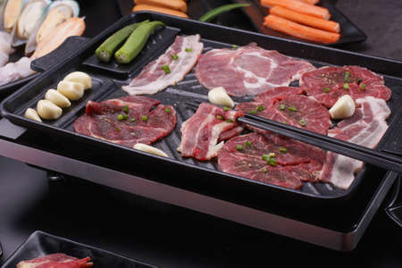 Raw beef slice for barbecue japanese style, yakiniku. Meats are being cooked on stove in a japanese restaurant. Standard-Bild - 157190314