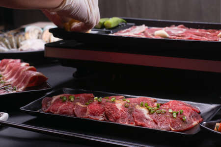 Food stylish prepare raw beef slice and seafood for barbecue japanese style, yakiniku, meat are being cooked on stove in Japanese restaurant. Standard-Bild - 157190326