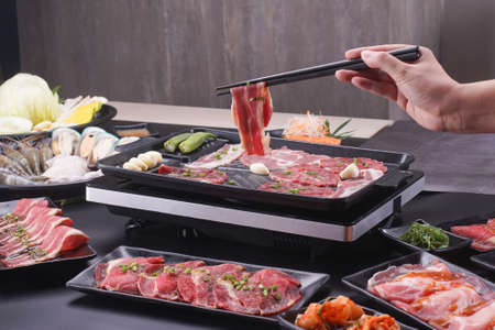 Food stylish prepare raw beef slice and seafood for barbecue japanese style, yakiniku, meat are being cooked on stove in Japanese restaurant.