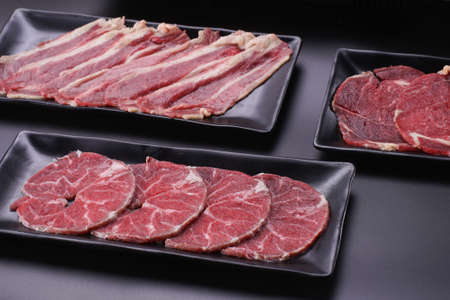 Raw beef slice for barbecue japanese style, yakiniku, meat are being cooked on stove in Japanese restaurant. Standard-Bild