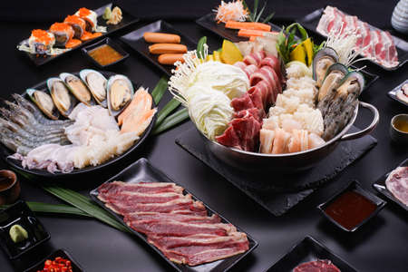 Shabu Shabu or Sukiyaki, a popular dish of pork, beef, shrimp, squid, seafood and fresh vegetables. Placed on a table with a boiling pot boiling in a Japanese restaurant. Standard-Bild - 157108692