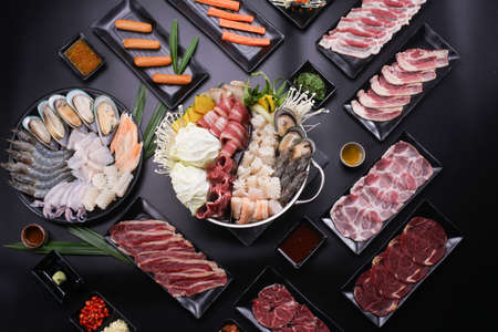 Shabu Shabu or Sukiyaki, a popular dish of pork, beef, shrimp, squid, seafood and fresh vegetables. Placed on a table with a boiling pot boiling in a Japanese restaurant. Standard-Bild - 157108635