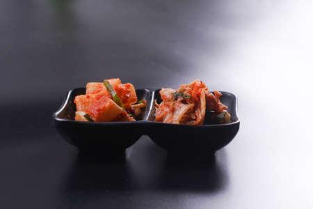 Kimchi cabbage in a black ceramic bowl on a black background. Korean food. Standard-Bild