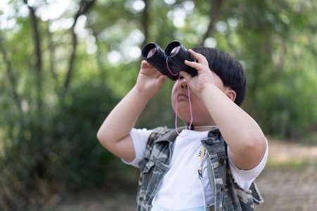 An adventure boy is using a binocular while he travels the jungle. Foto de archivo