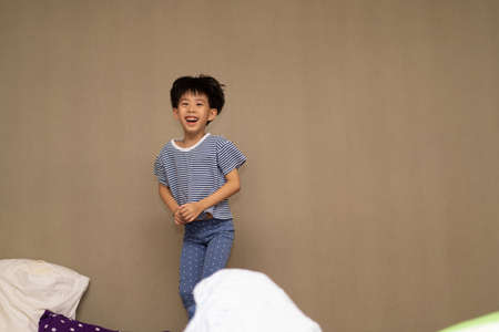 The boy is jumping on the bed at night. Stock Photo