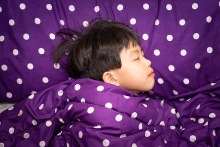A boy is sleeping on the bed at night. Stock Photo