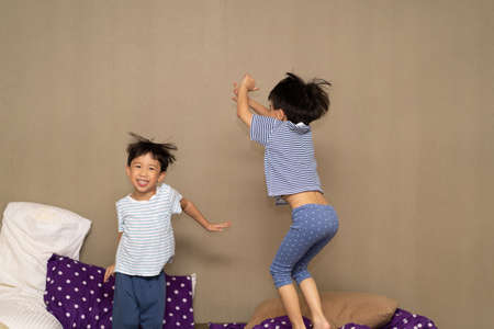 The brothers are jumping on the bed at night.
