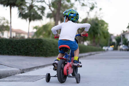 A happy boy is riding bicycle at the park.