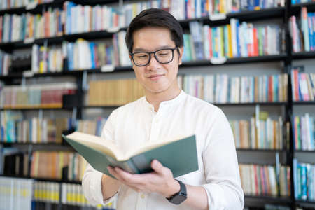 Asian man is reading a book in the university library.