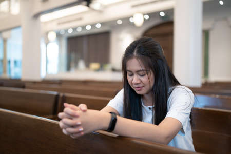 An Asian woman praying on a bench in a Christian church.