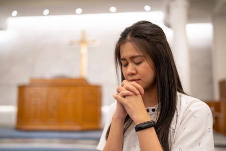 Asian women praying in a worship room in a Christian church.