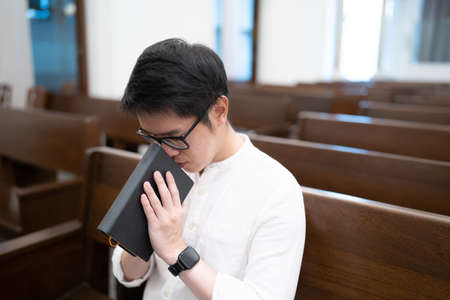 Asian man is reading the Holy Bible and praying in a worship room in a Christian church. Standard-Bild