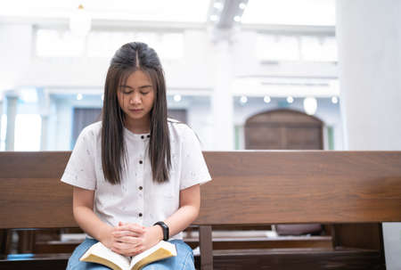 Asian woman is reading the Holy Bible and praying in a worship room in a Christian church. Standard-Bild