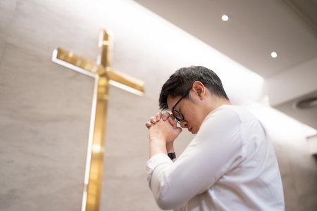 Asian man praying in a worship room in a Christian church.