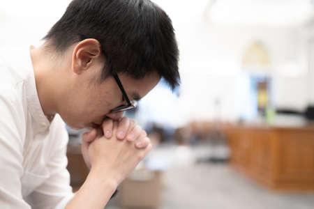 An Asian man praying on a bench in a Christian church. Standard-Bild