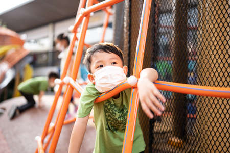 A boy is playing with face masks on playground during quarantine covid 19.
