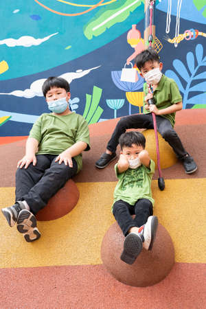 3 brothers are playing with face masks on playground during quarantine