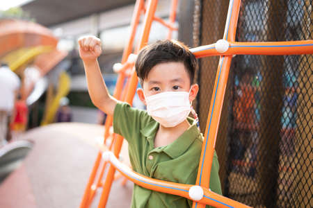 A boy is playing with face masks on playground during quarantine.