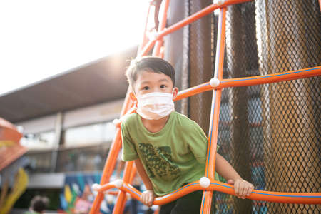 A boy is playing with face masks on playground during quarantine