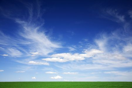 Green field, blue skies, white clouds in spring photo