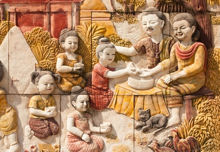 Stone carving of Thai culture of Songkran festival on temple wall photo