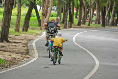 father and son riding bikes in park  photo