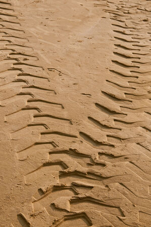 Tractor tire tracks on the sand photo