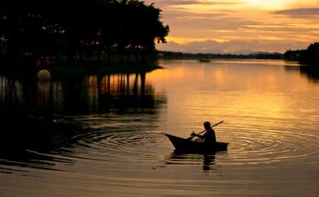 Silhouette of fisherman boating on the lake at sunset  photo