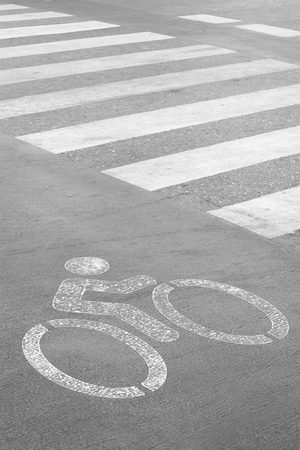 one lane road sign: Bicycle lane sign on the road with black and white image