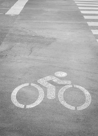one lane street sign: Bicycle lane sign on the road with black and white image