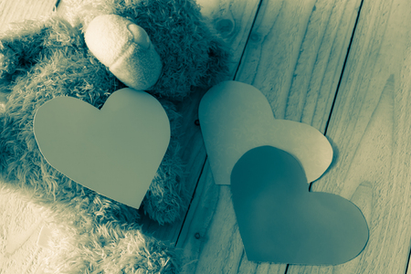 monotone: Teddy bear with shape hearts on wood background with monotone image