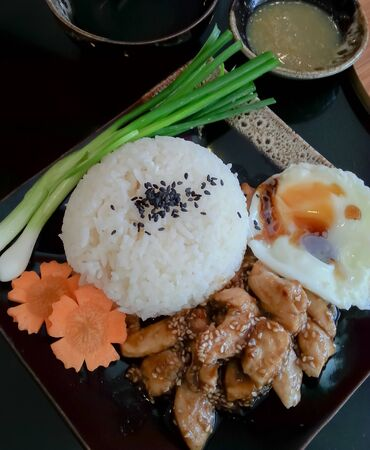 Rice serves with chicken and egg in teriyaki sauce on black background ,Japanese food Stock Photo
