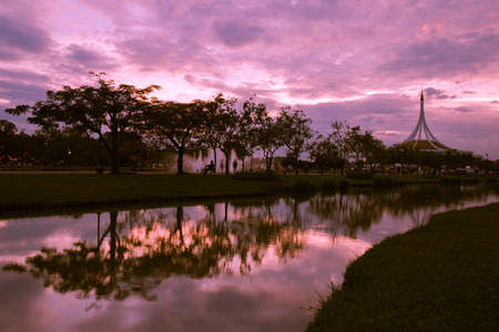 Dramatic sky with trees reflection in park