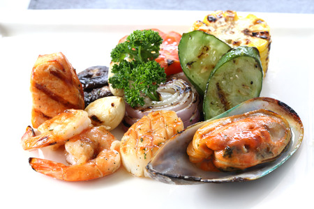 FRESH seafood: Grilled Seafood with roasted vegetables on white dish. International food Stock Photo