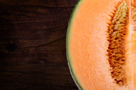 Organic cantaloupe on wooden table.