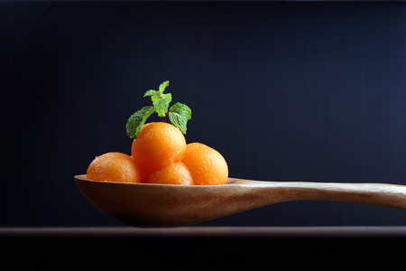 isoalated: Organic cantaloupe melon in wooden spoon isoalated on black background. Stock Photo