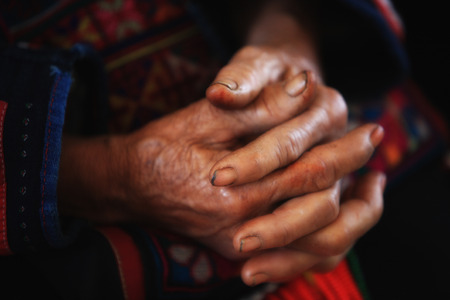 Old tribal woman with wrinkle hands clasped.