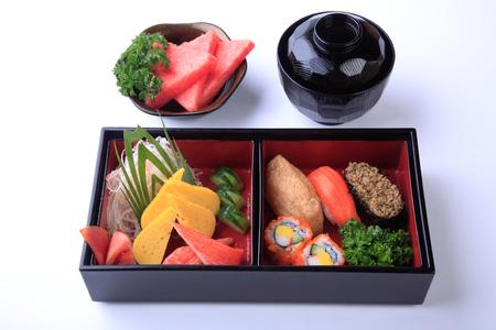 Sushi Set in wooden Bento (Japanese lunchbox) isolated on white background. Stock Photo
