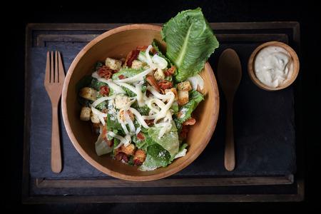 Organic caesar salad in wodden bowl with caesar dressing. International food.