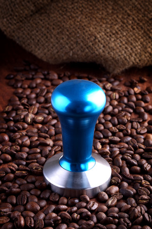 temper: Blue stainless steel coffee temper on wooden with roasted coffee beans. Stock Photo