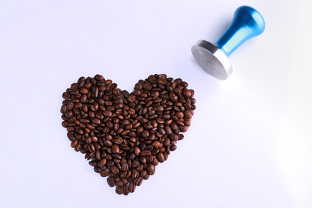 temper: Blue stainless steel coffee temper with roasted coffee beans in shape of heart on white background.