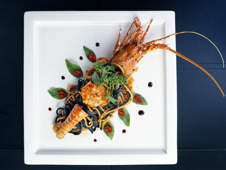 Top view of Pan fried two tone spaghetti with lobster on white plate, Thai style.