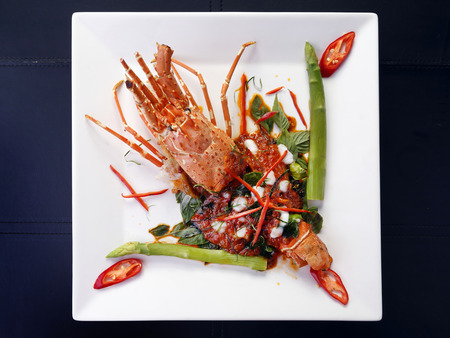 Thai style pan fried red curry with lobster on white plate, isolated on black background.