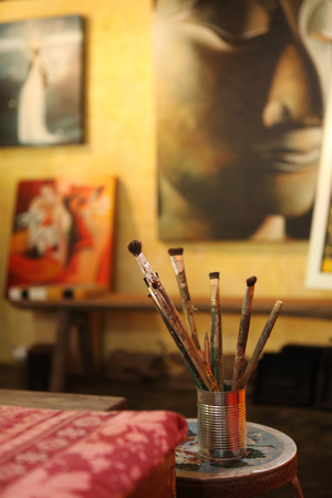 dirty room: Group of dirty artist paintbrushes in zinc can at art studio room.