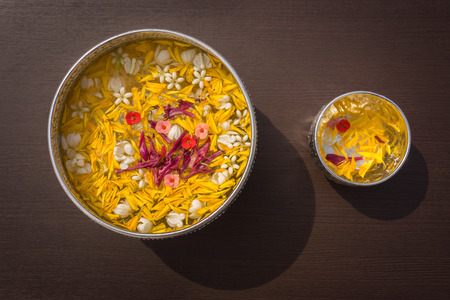 long weekend: Water in bowl mixed with perfume and vivid flowers corolla for Songkran festival in Thailand.