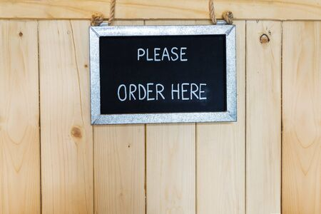 Order here sign hanging on wooden background